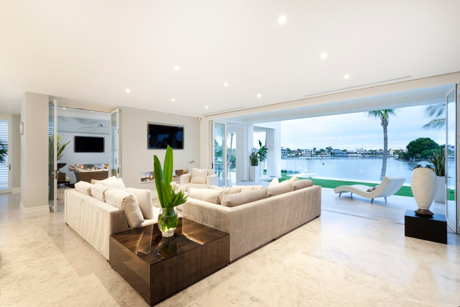 Beautiful living room with open doors to a yard viewing a big lake