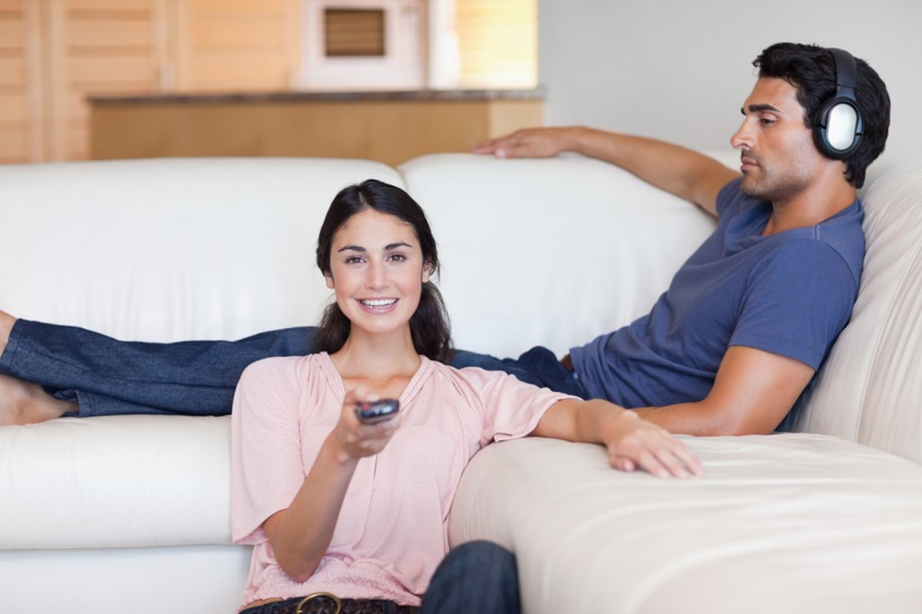 Woman watching television while her husband is listening to music in their living room