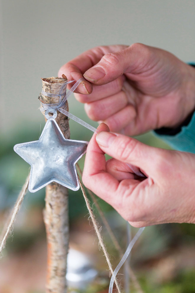 Close Up Detail Of Securing A Silver Star To The Pole Using A Fine Ribbon