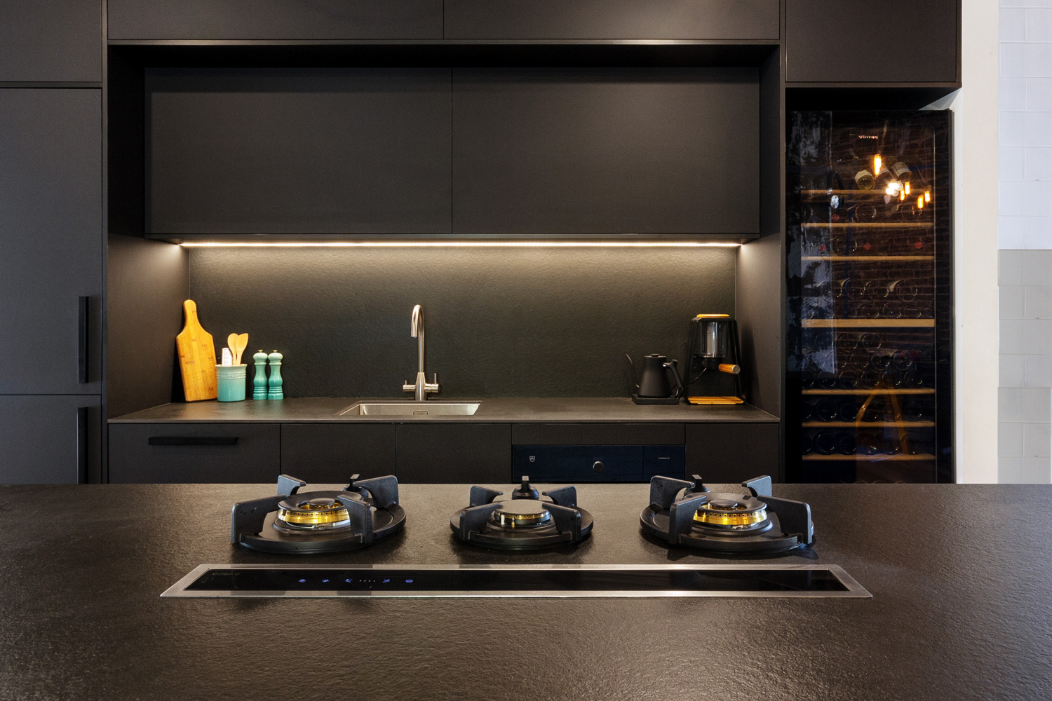 An all-black kitchen that combines industrial style and modern finesse