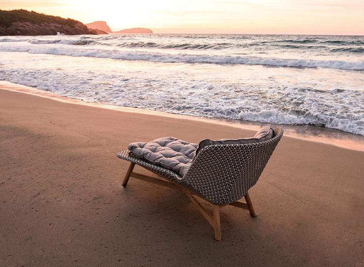 The MBRACE Daybed by DEDON, sitting happily on the seashore as the sun sets.