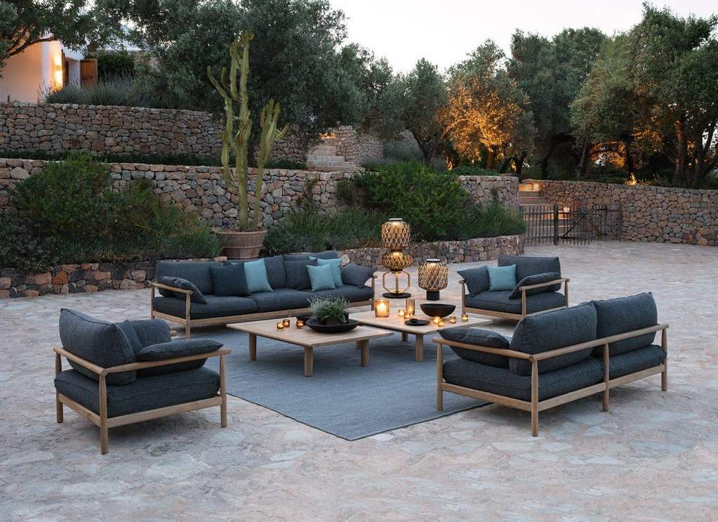 An outdoor setting, featuring the TIBBO Sofa, Lounge Chair, Coffee Tables and THE OTHERS outdoor lighting.