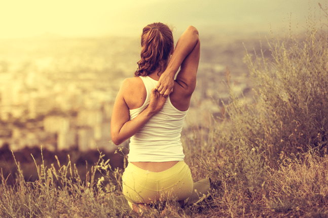Young woman sits in yoga pose with city on background