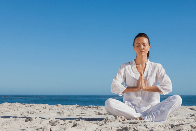 Peaceful woman meditating on the beach
