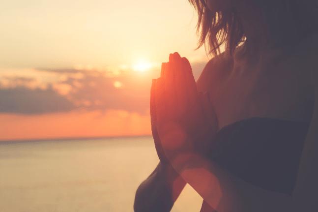 Woman doing namaste at sunset