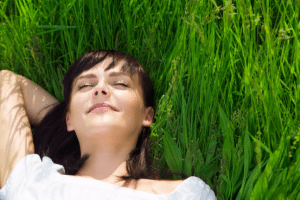 Woman relaxing/sleeping in grass happy