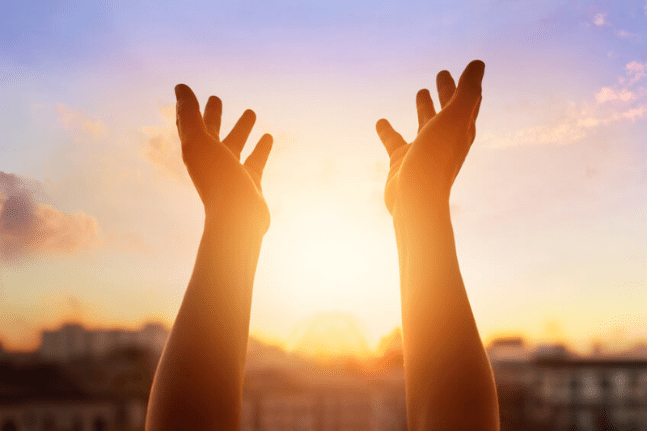 Hands being held up towards a sunrise