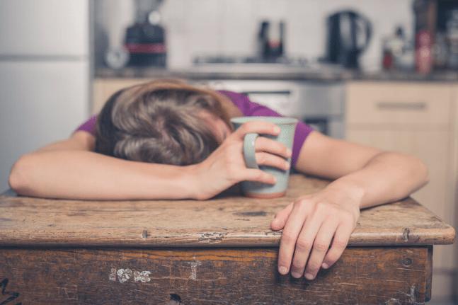 Woman asleep with coffee cup