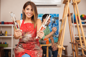 Woman holding paintbrushes