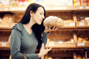Woman smelling bread in supermarket