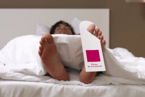 Man sleeping with 'do not disturb' sign on his toe