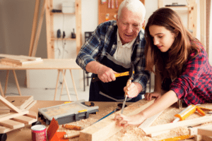 Girl with grandfather at workshop