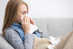 Woman blowing nose sick