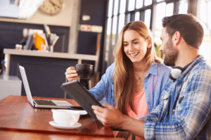 Young man and woman at coffee shop using technology