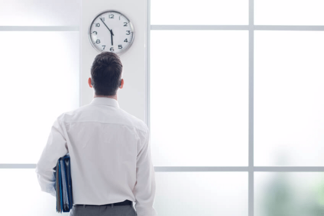 Businessman staring at clock in office