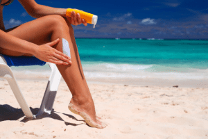 Woman applying sunscreen to her legs at beach