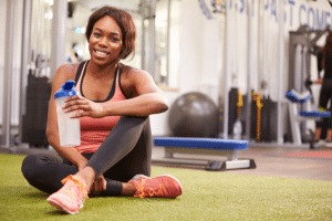 Happy woman drinking water at the gym