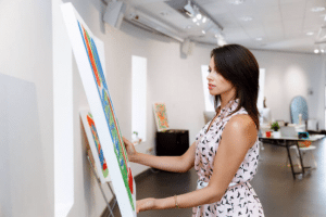 Woman hanging up artwork in studio