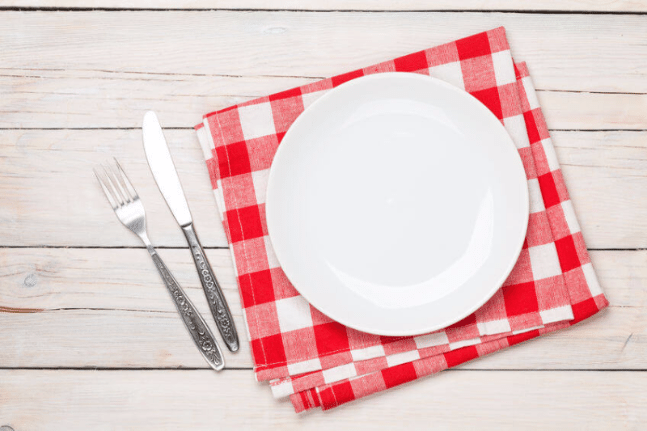 Empty plate with silverware on wooden table