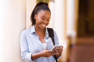 Young woman texting on her phone smiling