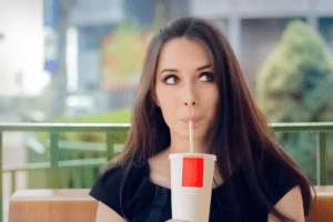 Young woman drinking a sugary drink outside