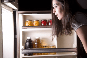 Woman looking through her fridge at night