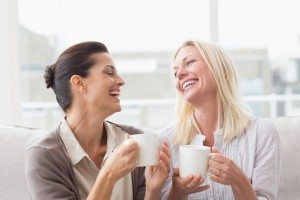 Cheerful women gossiping while having coffee in living room