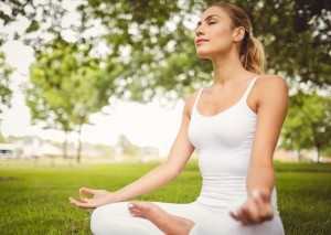 Woman meditating while sitting in lotus pose at park