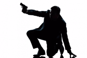 Spy kneeling on ground with gun raised
