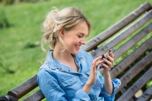 44251745 - cute blonde in a bright blue denim shirt emotionally talking on a cell phone.