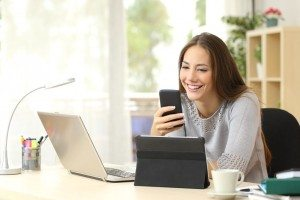 50532388 - happy woman working using multiple devices on a desk at home