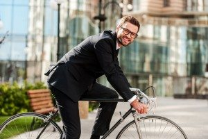 Side view of cheerful young businessman looking at camera and smiling while riding on his bicycle