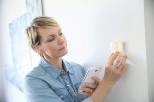 woman adjsuting temperature of air conditioner with smart phone