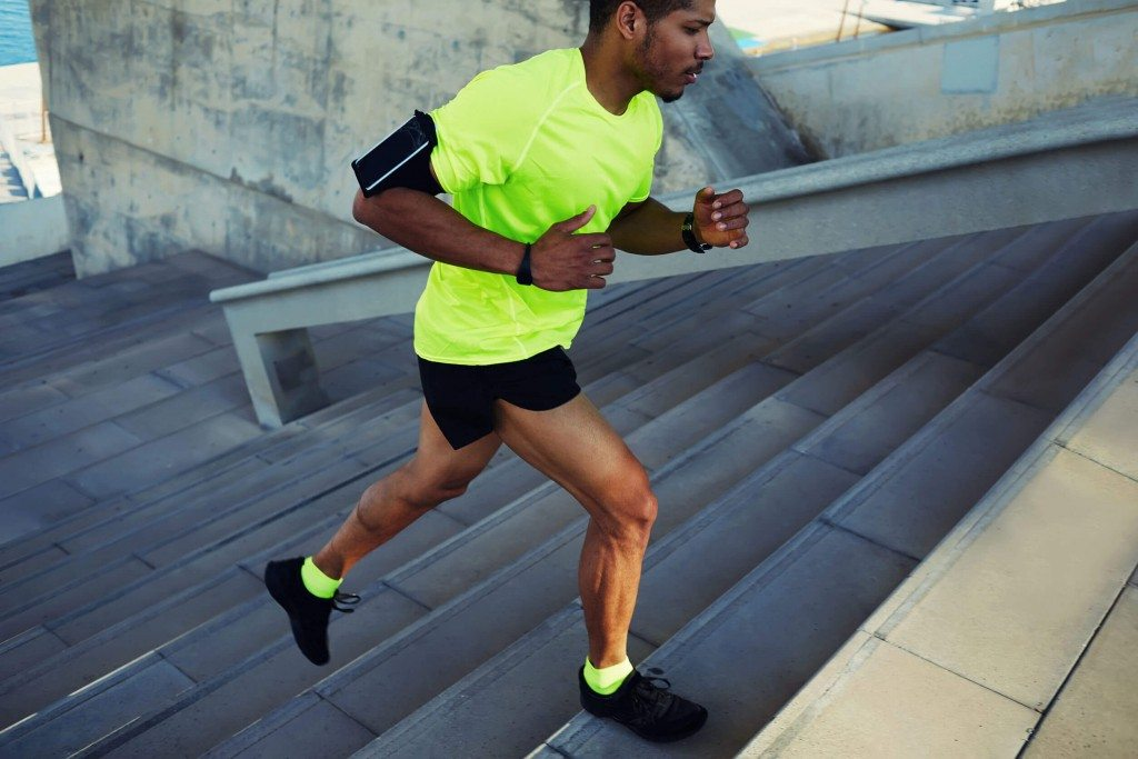 male athlete running up a flight of stairs