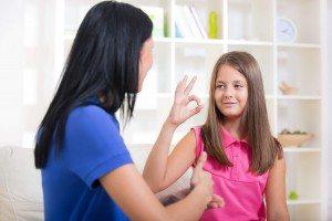 smiling deaf girl using sign language