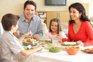 Young Family Enjoying Meal At Home