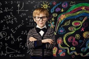child standing in front of blackbaord with drawing and mathematical formula