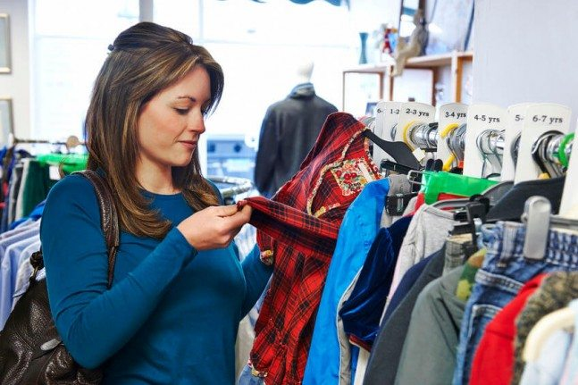 woman shopping clothes at a charity shop