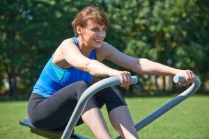 Mature Woman Exercising On Rowing Machine In Park