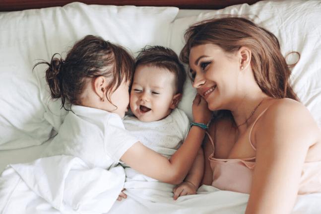 Mum and daughters hugging in bed