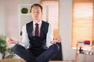 Calm businessman meditating in lotus pose in his office
