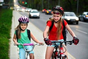 Girl children cycling with traffic on street