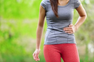 woman runner holding her stomach in pain