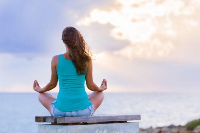 woman meditating facing the ocean