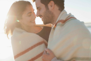 Smiling couple wrapped in blanket and hugging on beach love happy