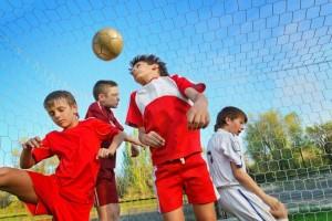 adolescent boys playing soccer near a goal