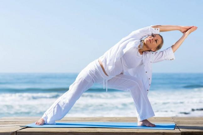 woman practising yoga on the beach