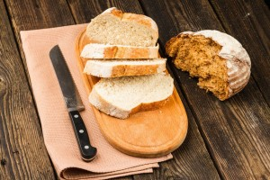 fresh white bread and brown bread on wooden background