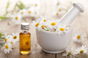 17665524 - essential oil and camomile flowers in mortar