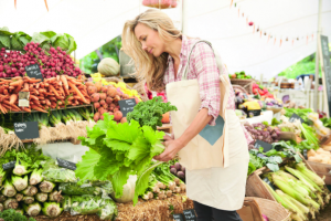 Female Customer Shopping At Farmers Market Stall